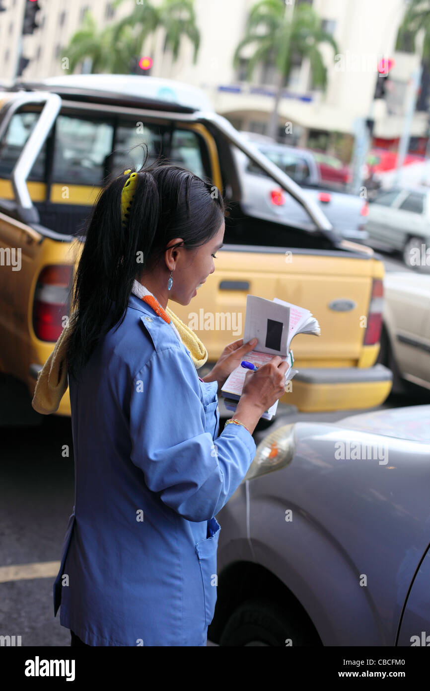 Attractive traffic warden writing out parking tickets. Kota Kinabalu, Sabah, Borneo, Malaysia, South-East Asia, - Stock Image