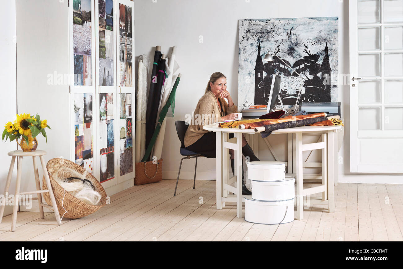 Designer sitting at computer in office - Stock Image