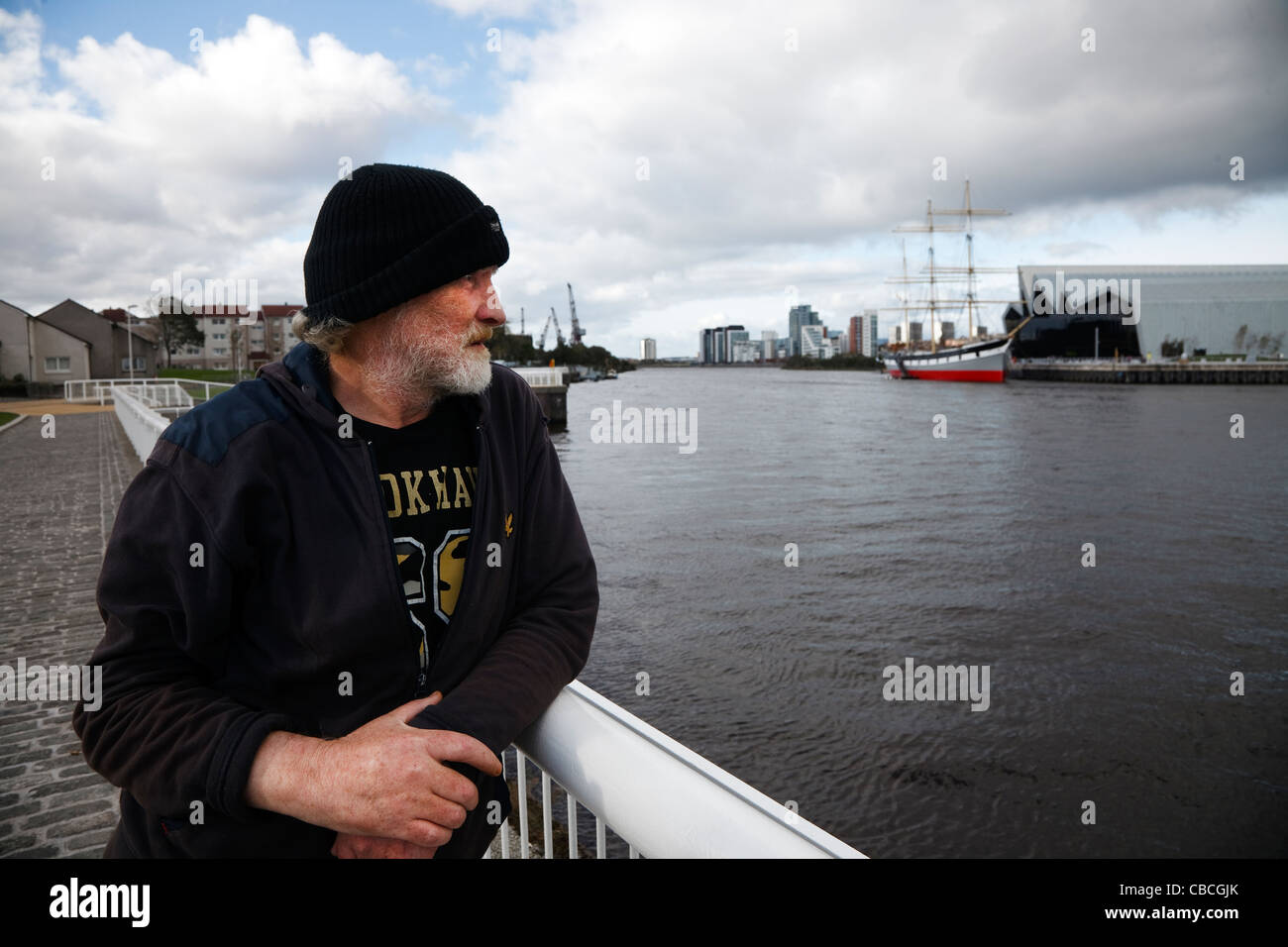 Unemployed Adult man looking over railings from a walkway in Govan, across the River Clyde to the new Riverside - Stock Image