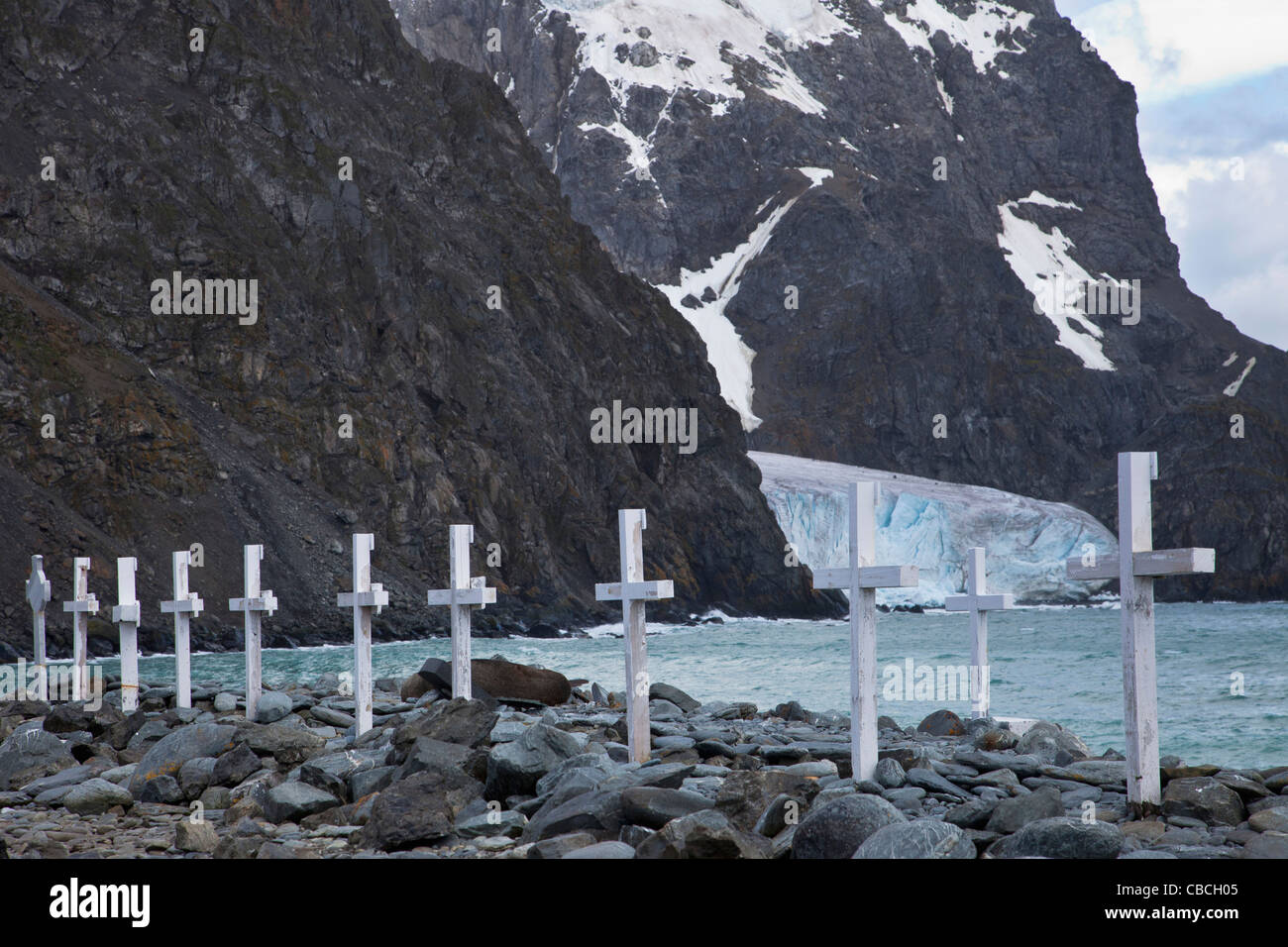 South Orkney Islands, Laurie Island. Grave markers in stony beach, with glacier and rock cliffs in the background Stock Photo