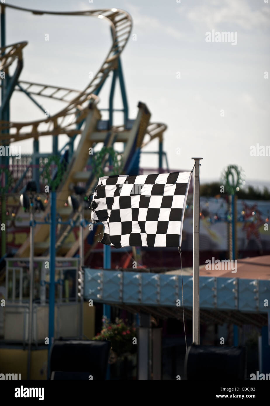 A black and white chequered flag fluttering in strong wind - Stock Image