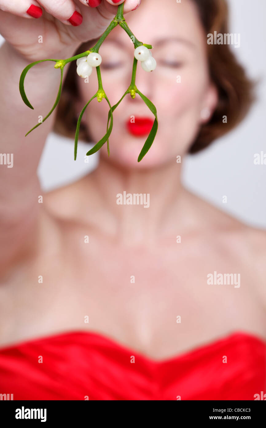 Photo of a woman in a red dress holding some mistletoe and kissing with her eyes shut. - Stock Image