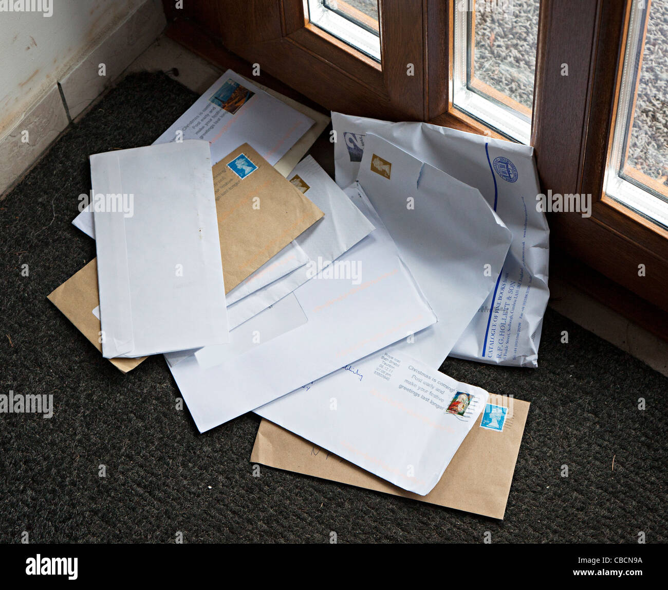 Letters delivered to house in heap on doormat Wales UK - Stock Image
