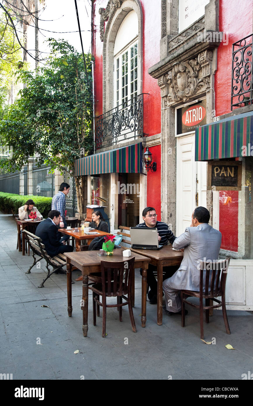 charming sidewalk cafe in a beautiful old building with people seated outdoors on a quiet street in Roma District - Stock Image
