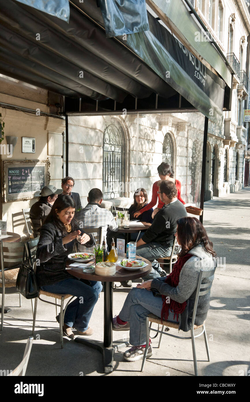 groups of casually dressed young people enjoy eating outside at charming old world sidewalk cafe Roma district Mexico - Stock Image