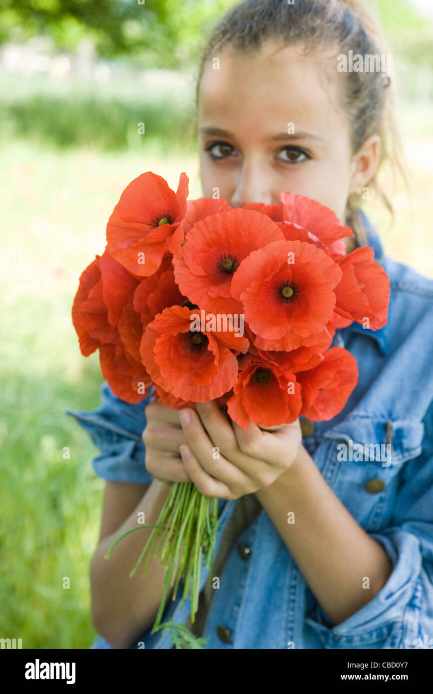 Teen girl smelling bouquet of fresh poppies - Stock Image