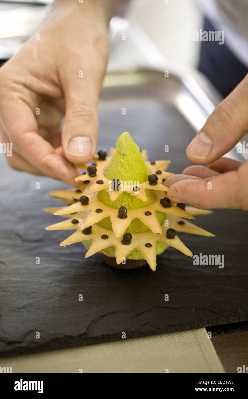 Chef assembling dessert shaped like Christmas tree - Stock Image