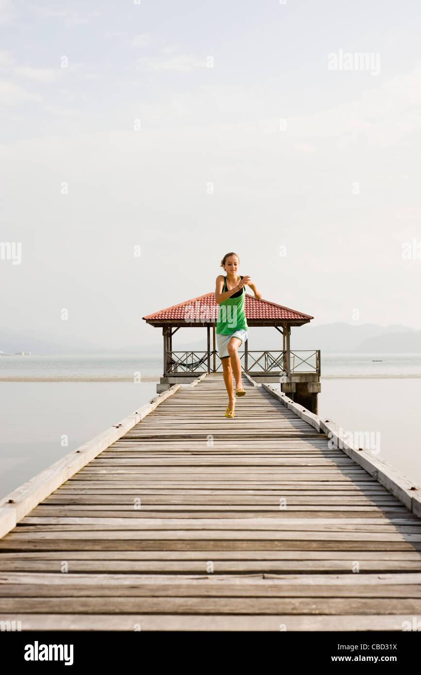 Preteen girl running on pier Stock Photo