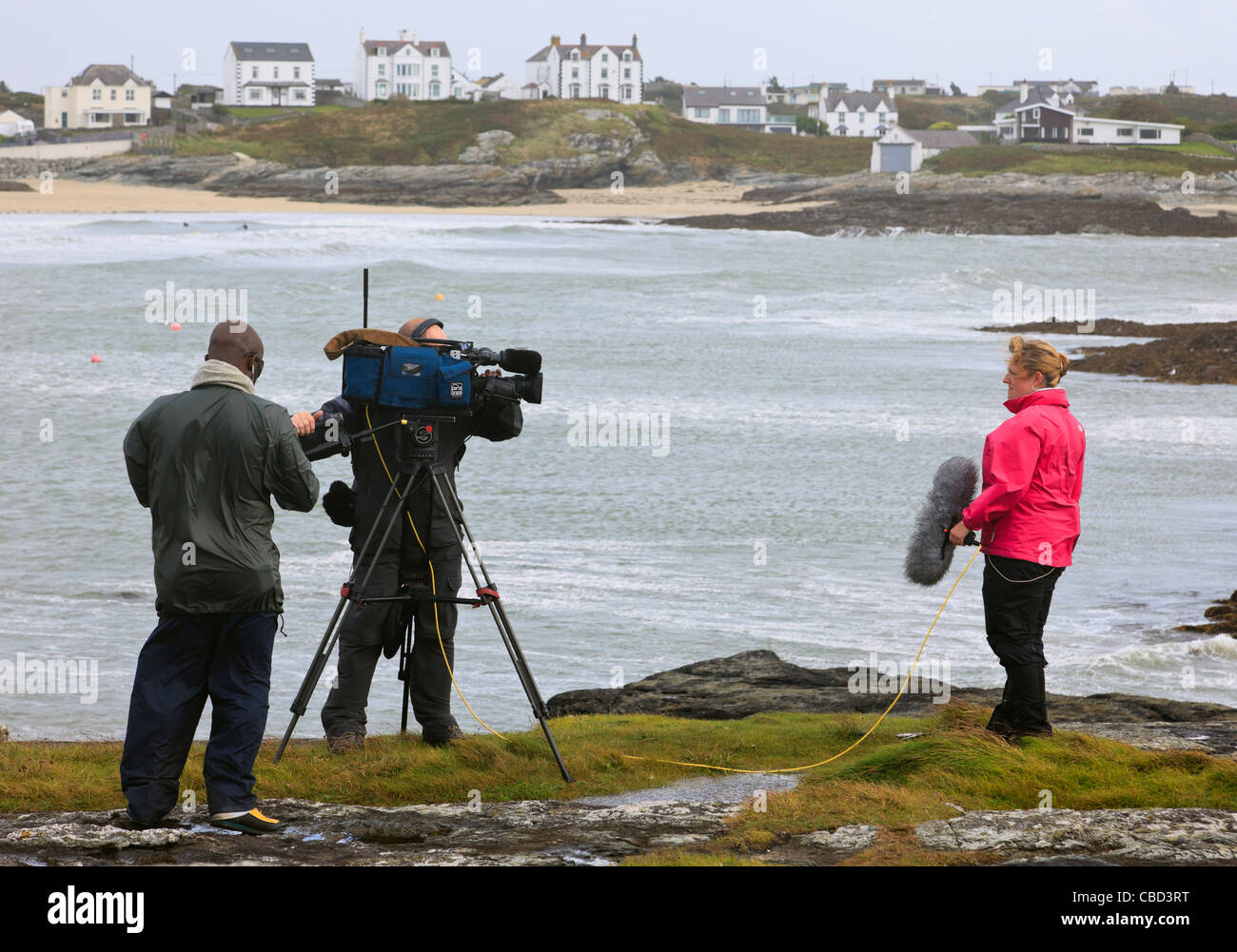 UK BBC live news reporter and camera crew reporting severe windy weather with gales on Welsh west coast. - Stock Image
