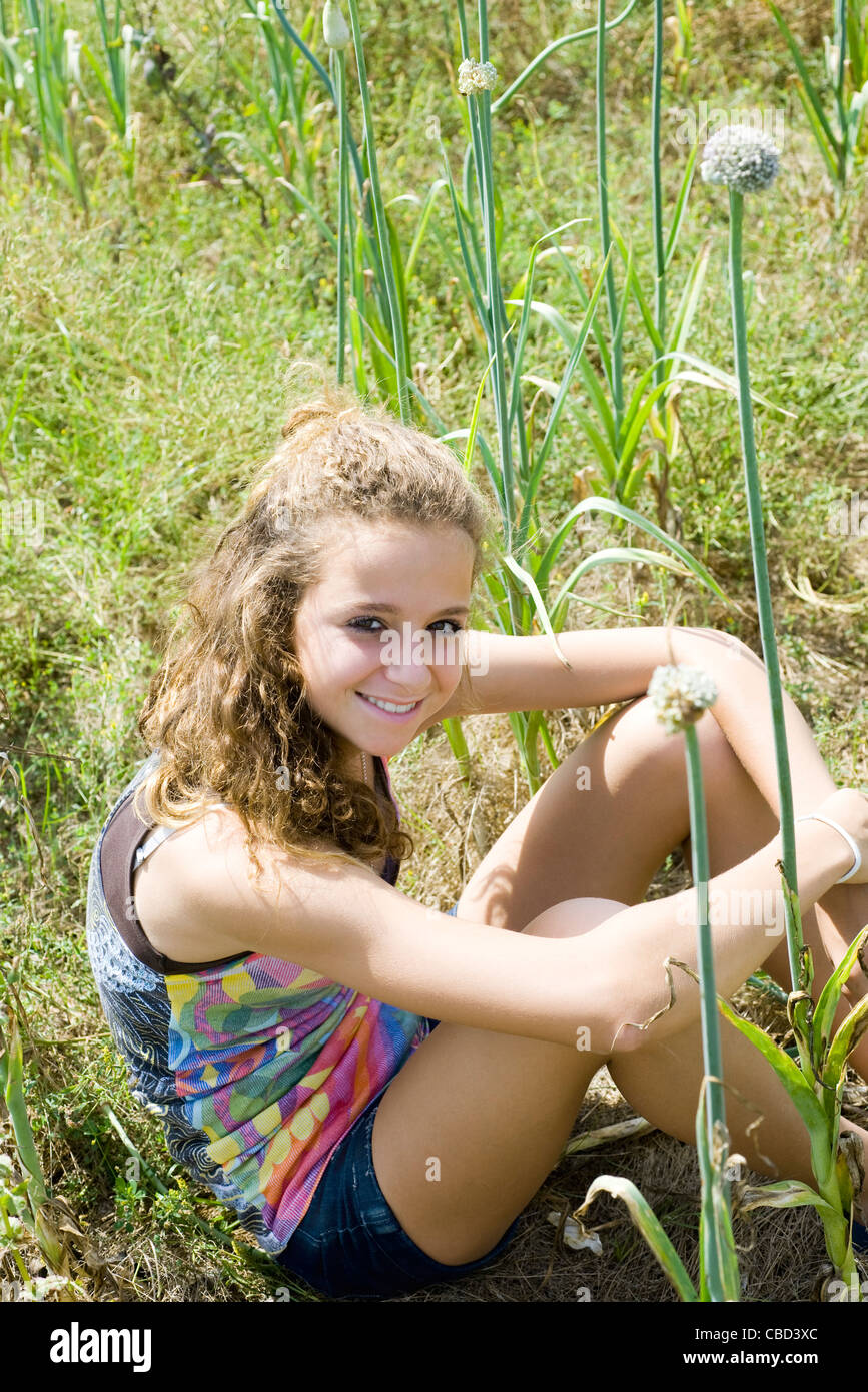 Teen girl sitting in field of garlic flowers - Stock Image