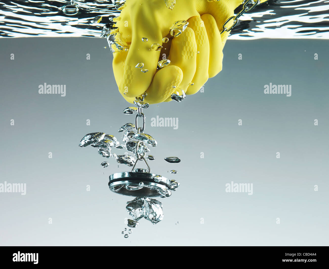 Rubber glove pulling plug in water - Stock Image