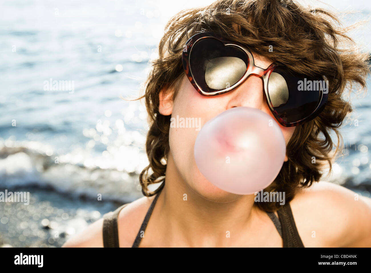 Woman blowing bubble on beach - Stock Image