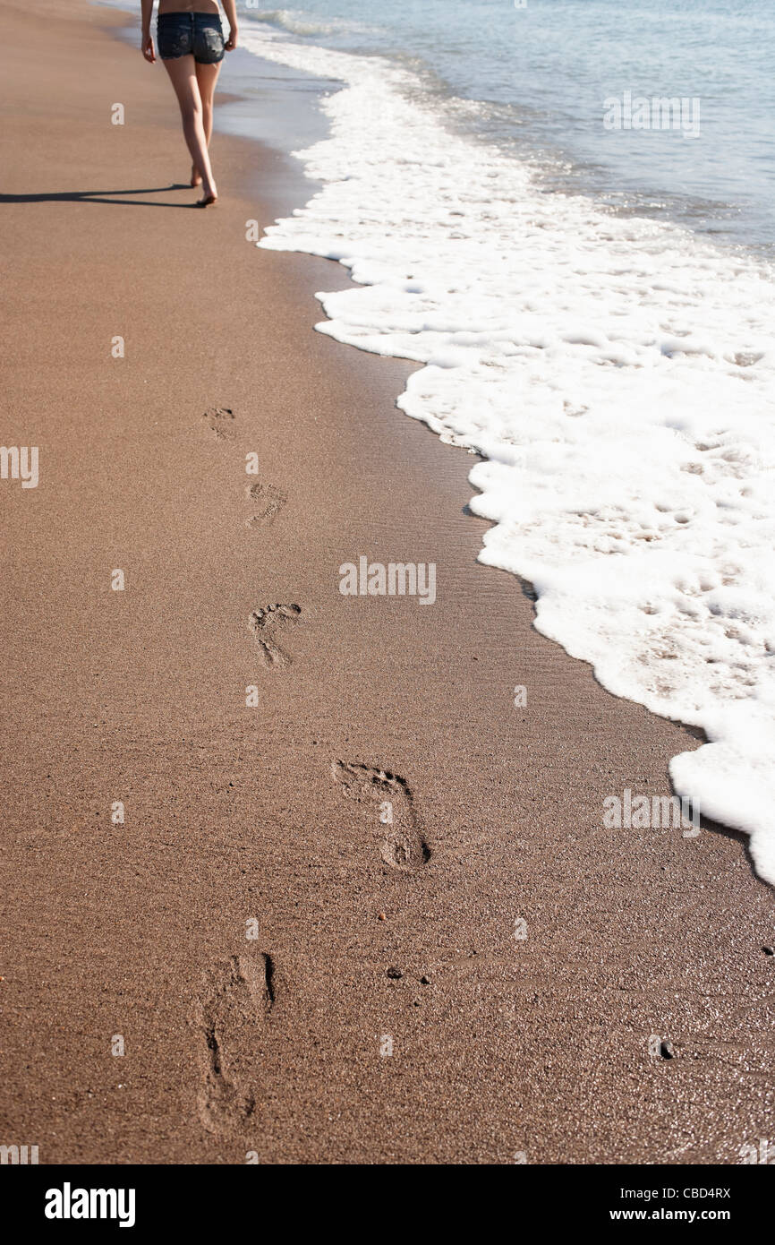 Woman's footprints on beach - Stock Image