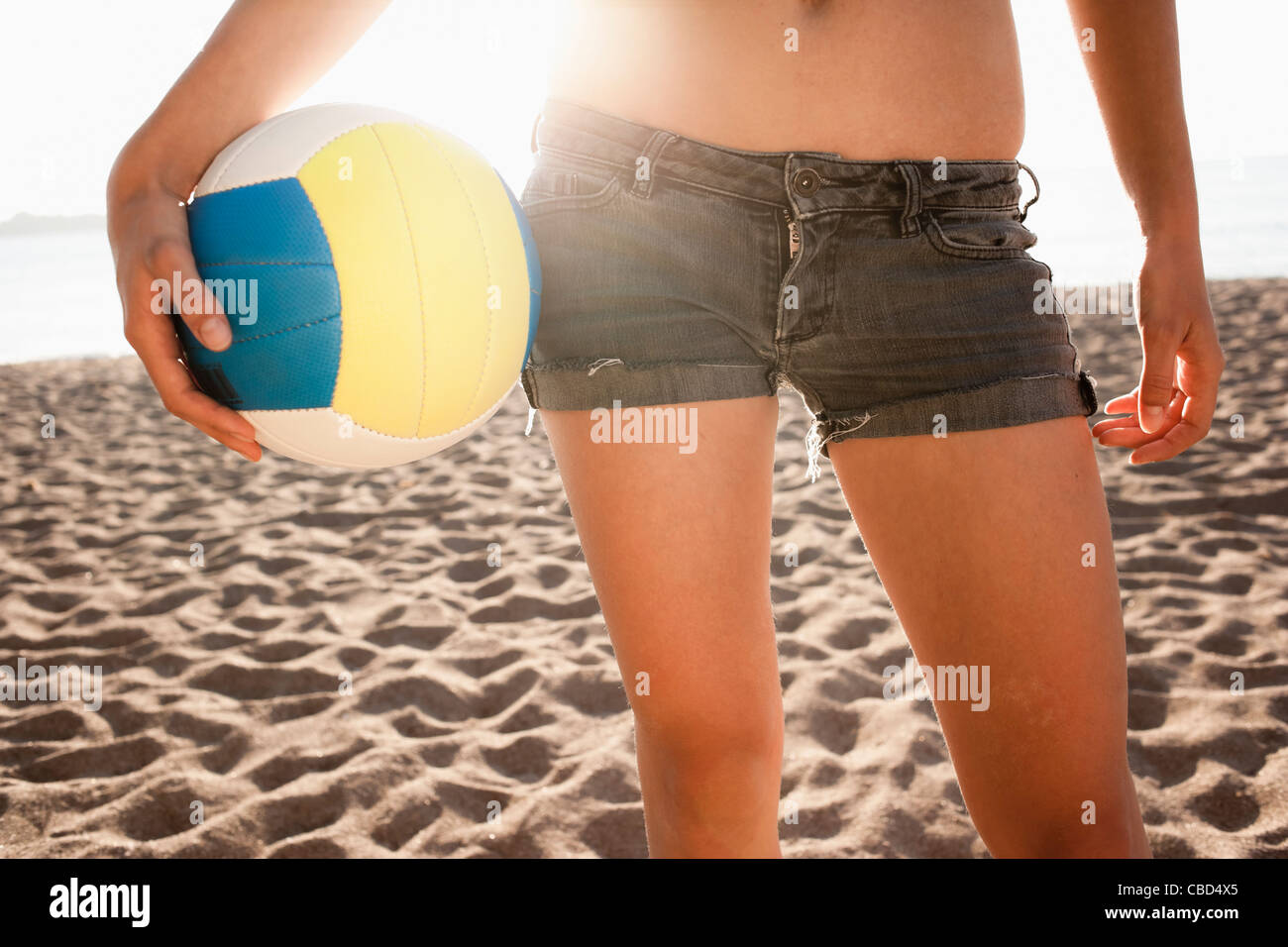 Woman holding volleyball on beach - Stock Image