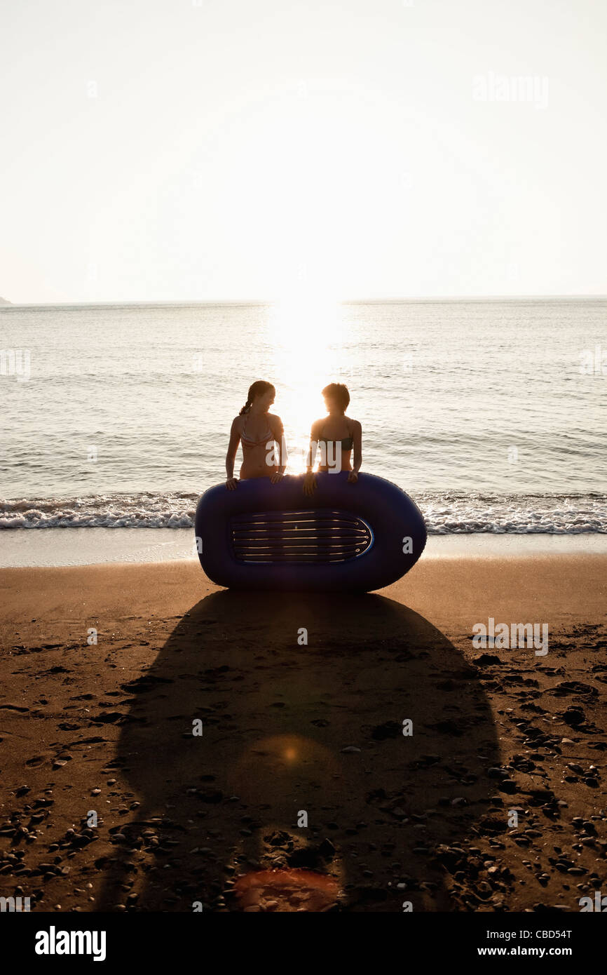 Women with inflatable boat on beach - Stock Image