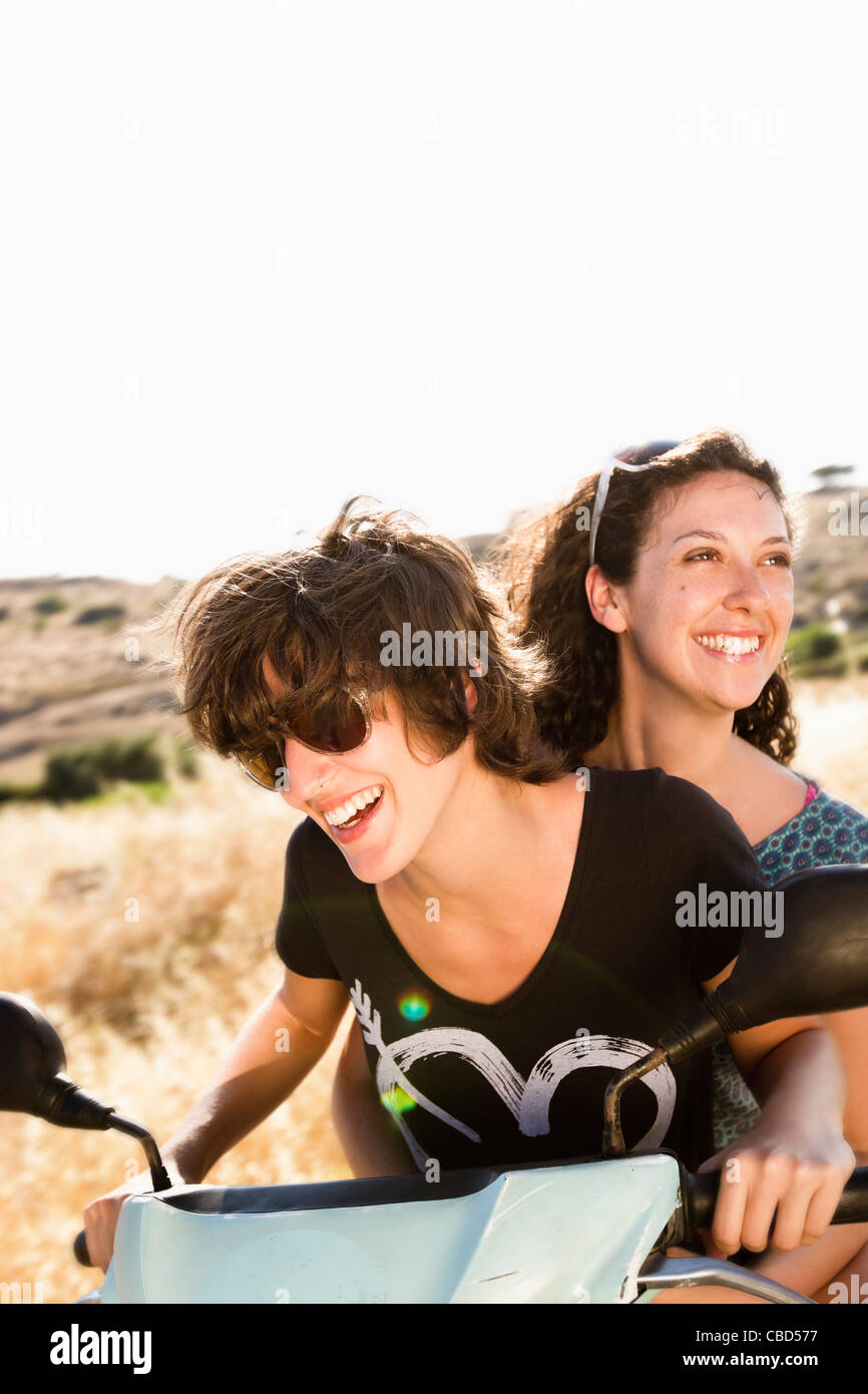 Smiling women riding scooter together - Stock Image