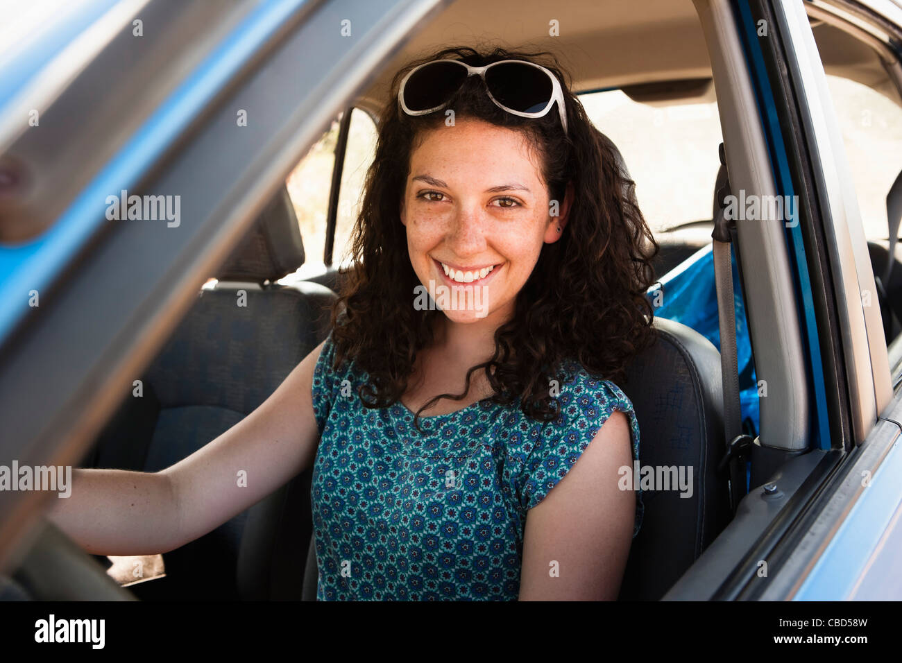 Smiling woman driving car - Stock Image