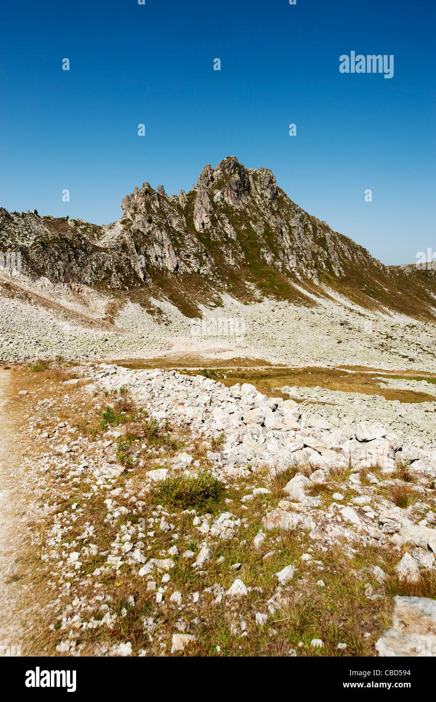 Rough track over sunbaked scree covered slopes in the French Savoie alps above Lac des Inversens at La Plagne in - Stock Image