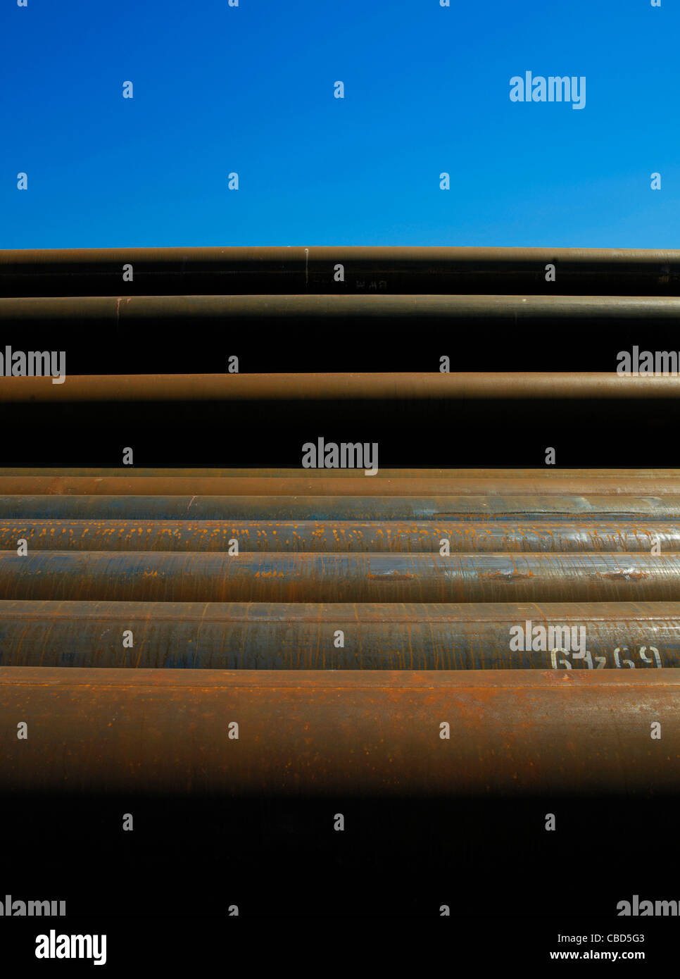 Rusted pipes piled against blue sky - Stock Image