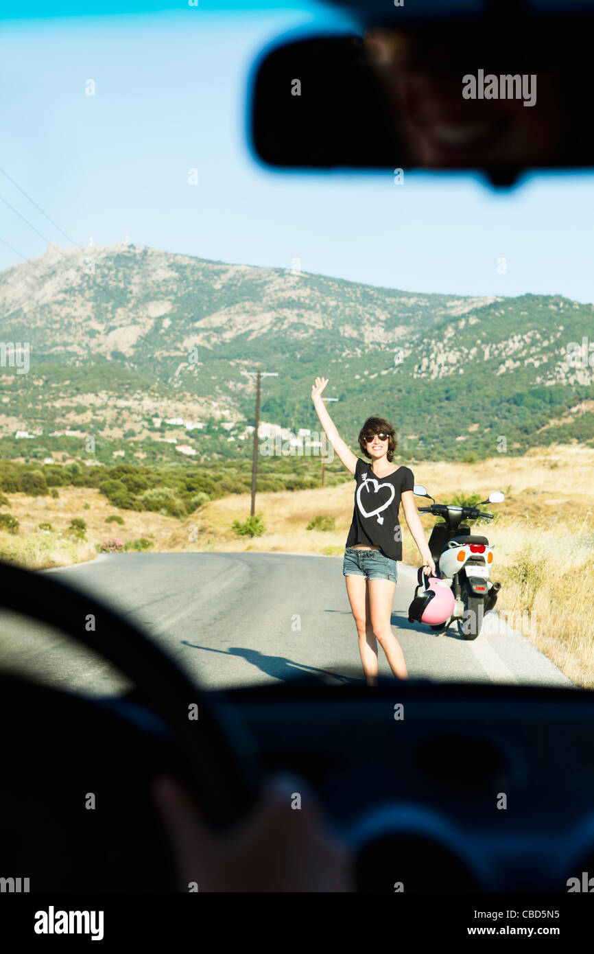 Woman with broken down scooter on road - Stock Image