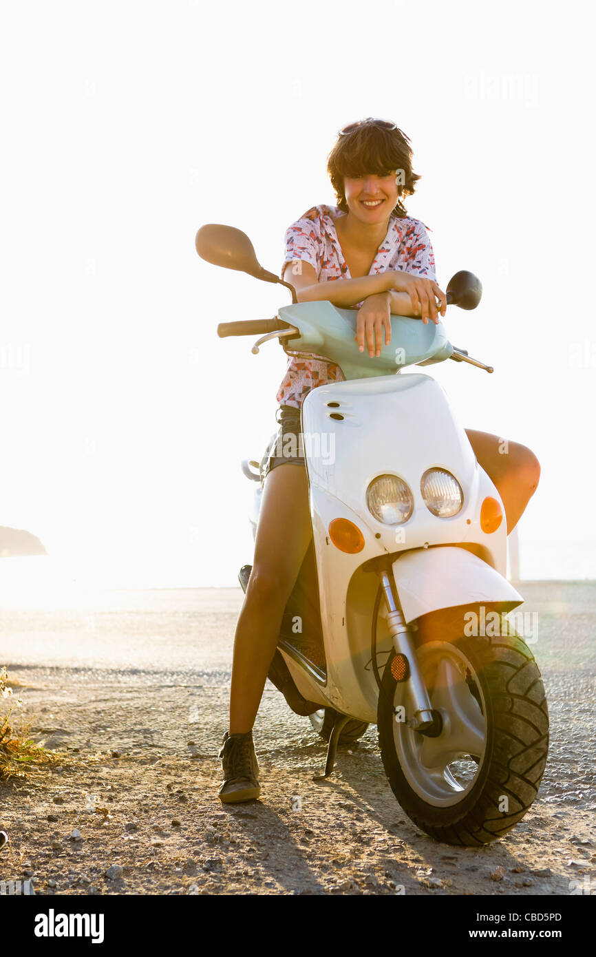 Woman sitting on scooter on beach - Stock Image