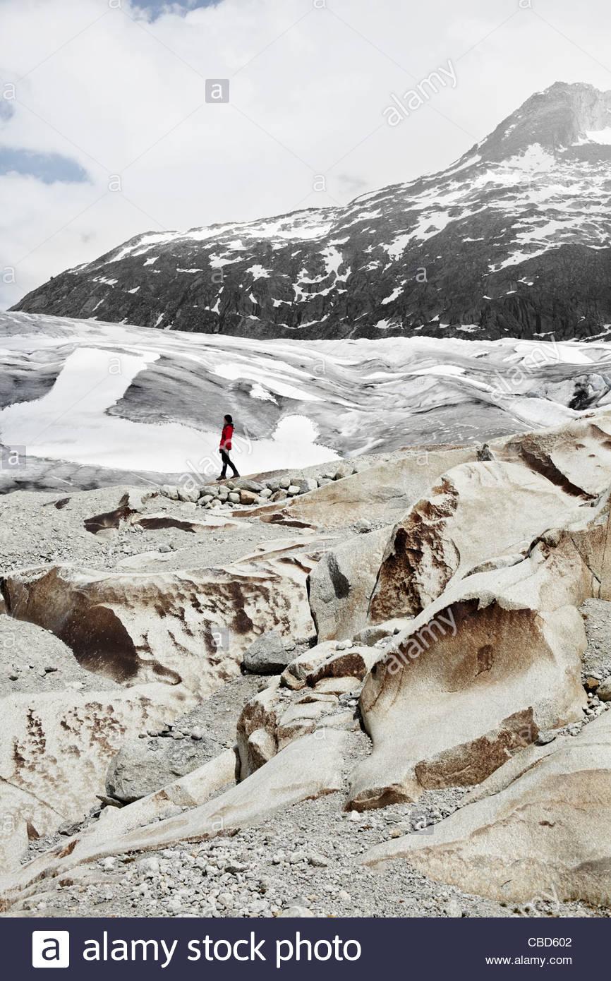 Woman walking in glacial landscape Stock Photo
