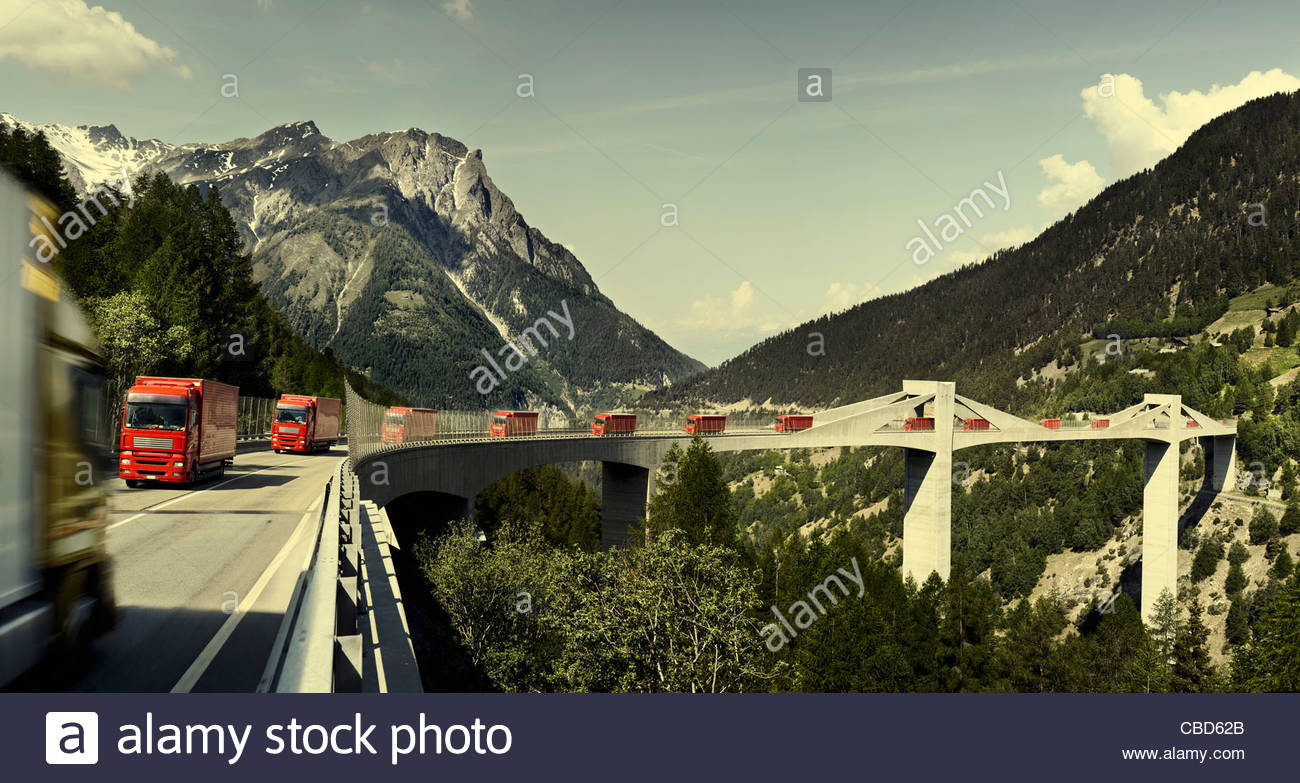 Trucks driving on bridge in mountains - Stock Image