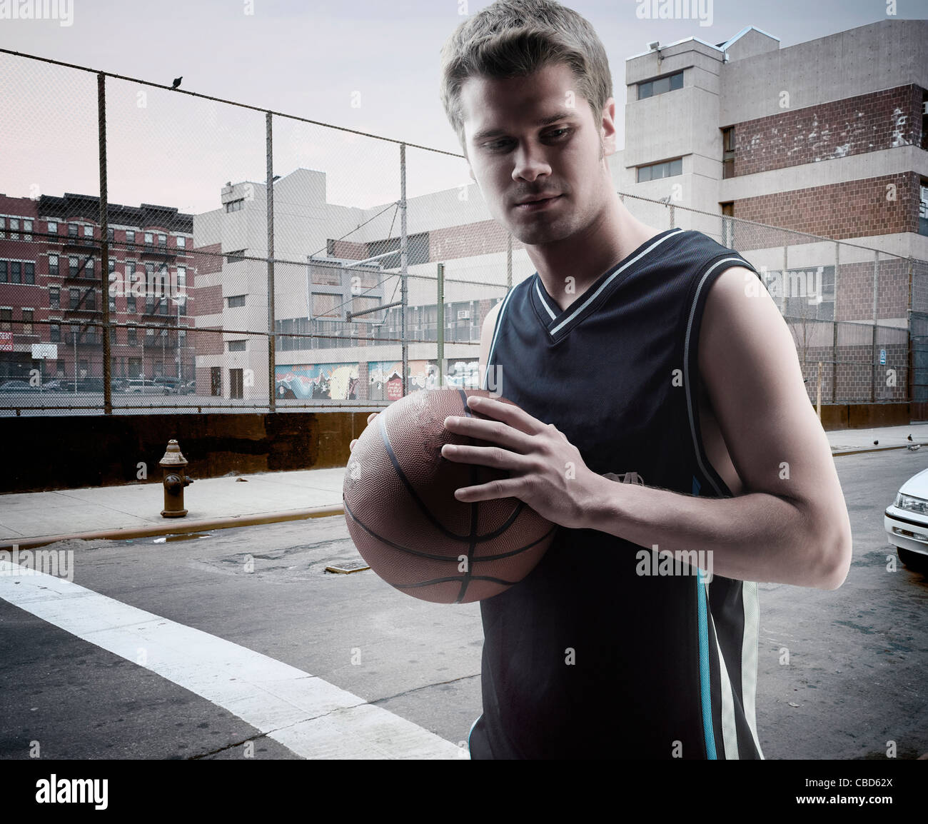 Man carrying basketball on city street - Stock Image
