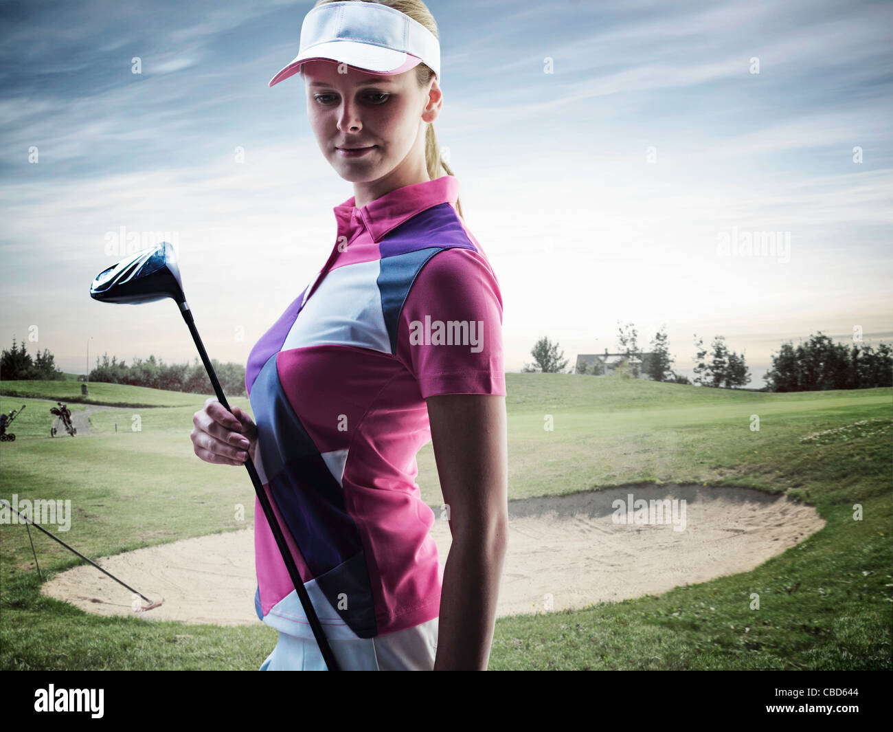 Woman carrying golf club on course - Stock Image