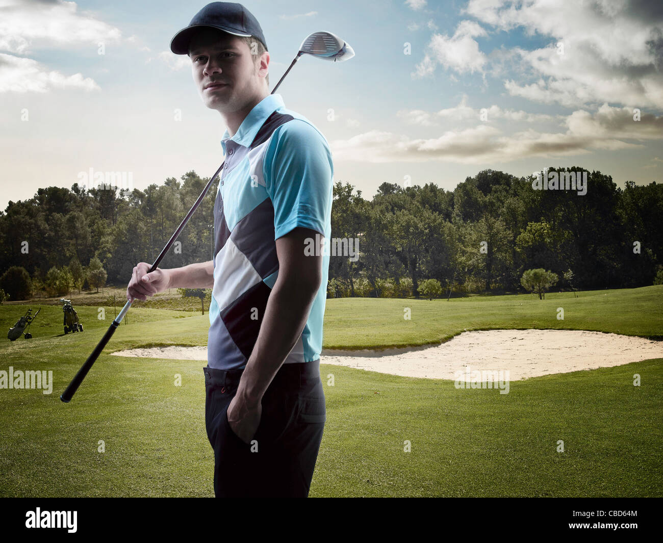 Man carrying golf club on course - Stock Image