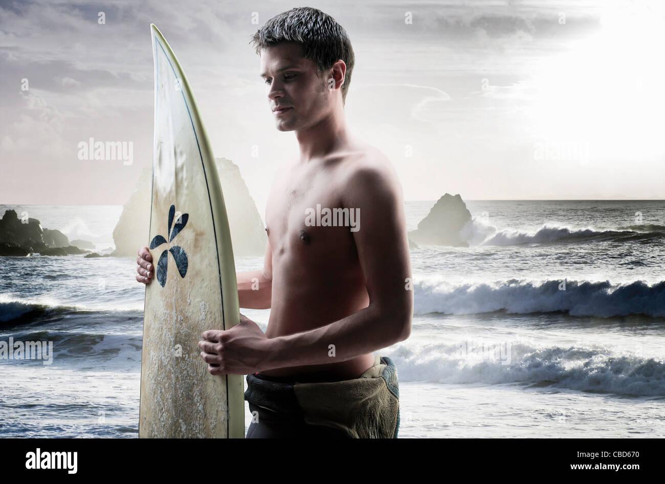 Man carrying surfboard on beach Stock Photo