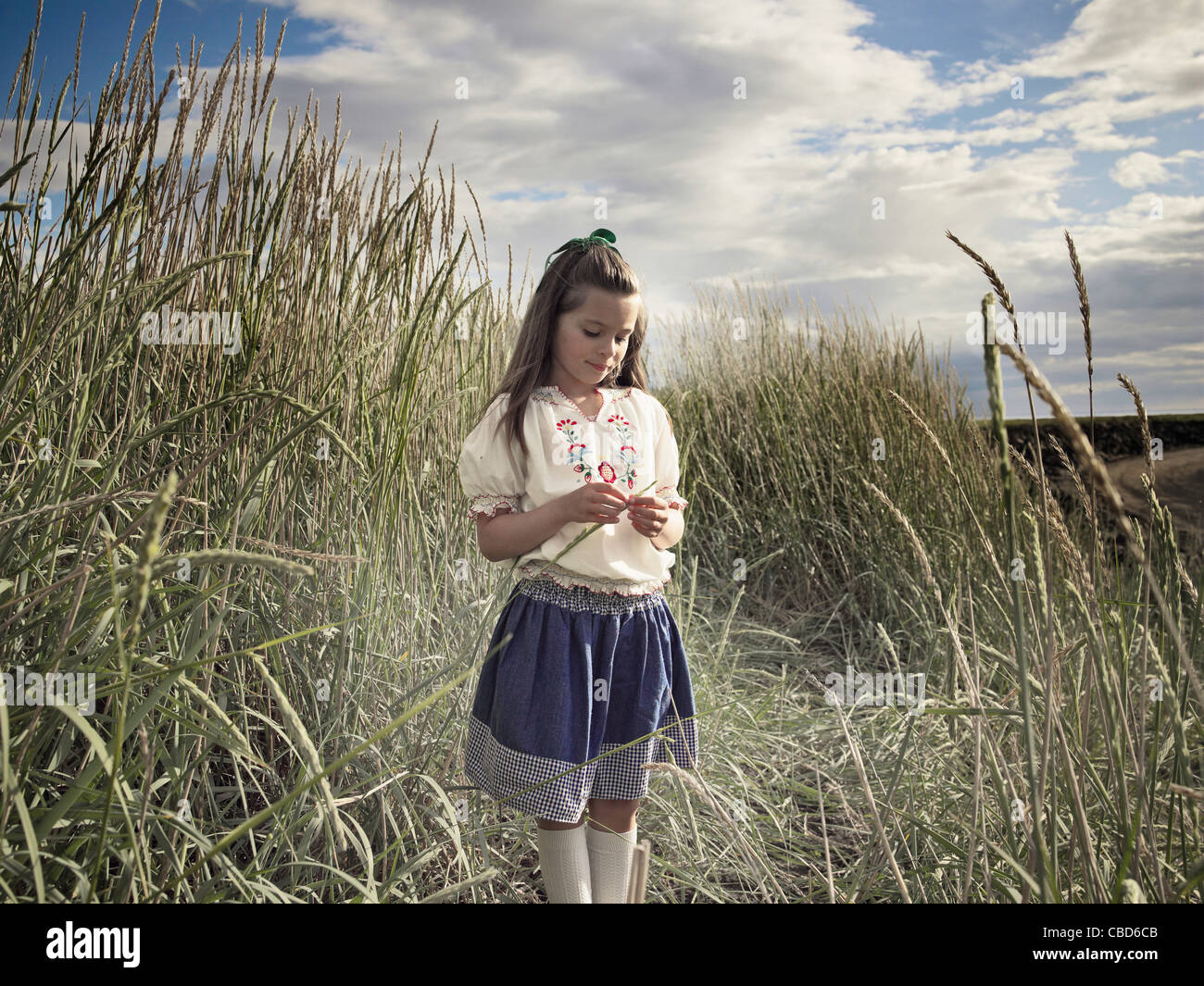 Girl playing in wheatfield - Stock Image