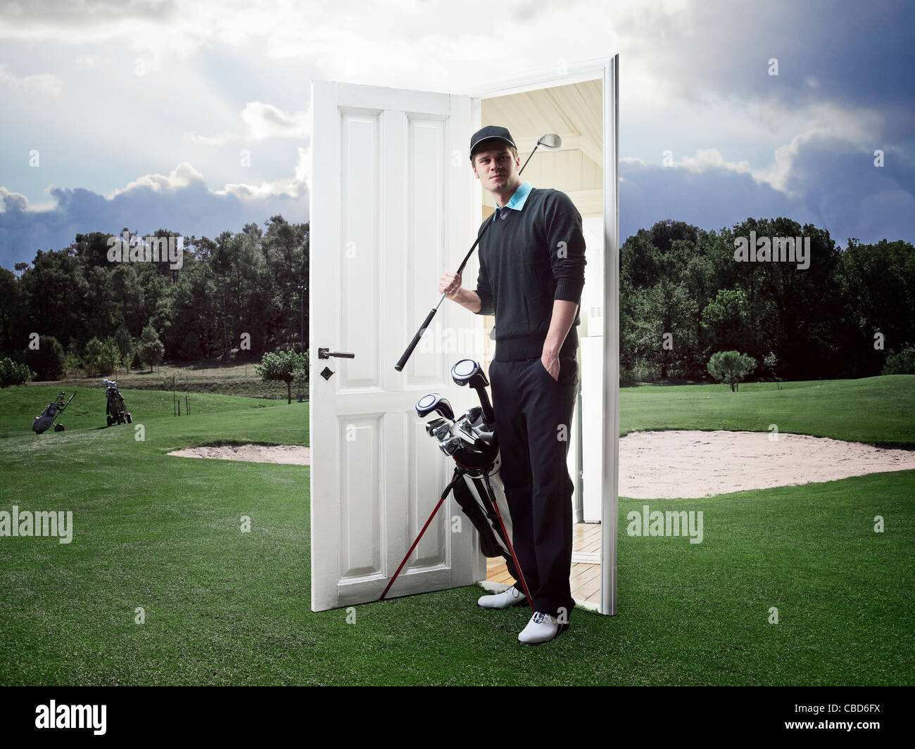 Man emerging from door on golf course - Stock Image