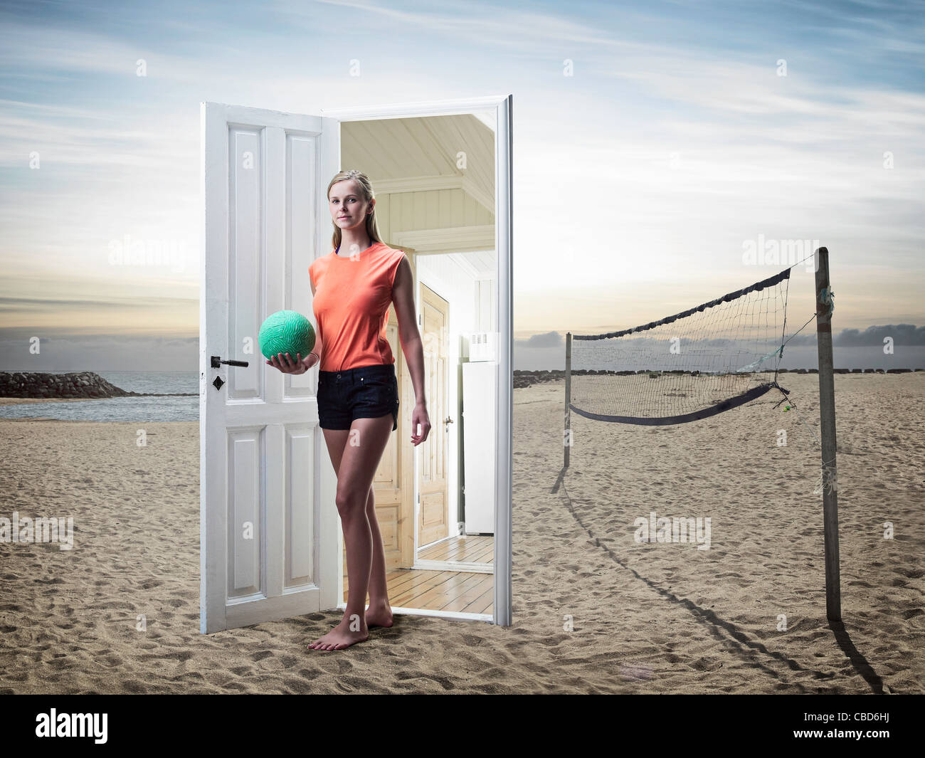 Woman emerging from door on beach - Stock Image