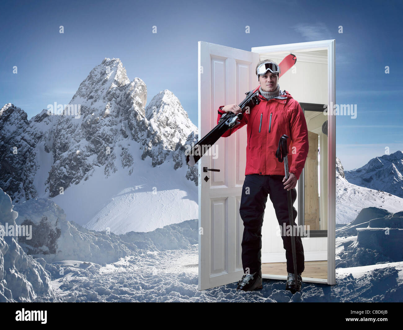 Skier emerging from door in mountains - Stock Image