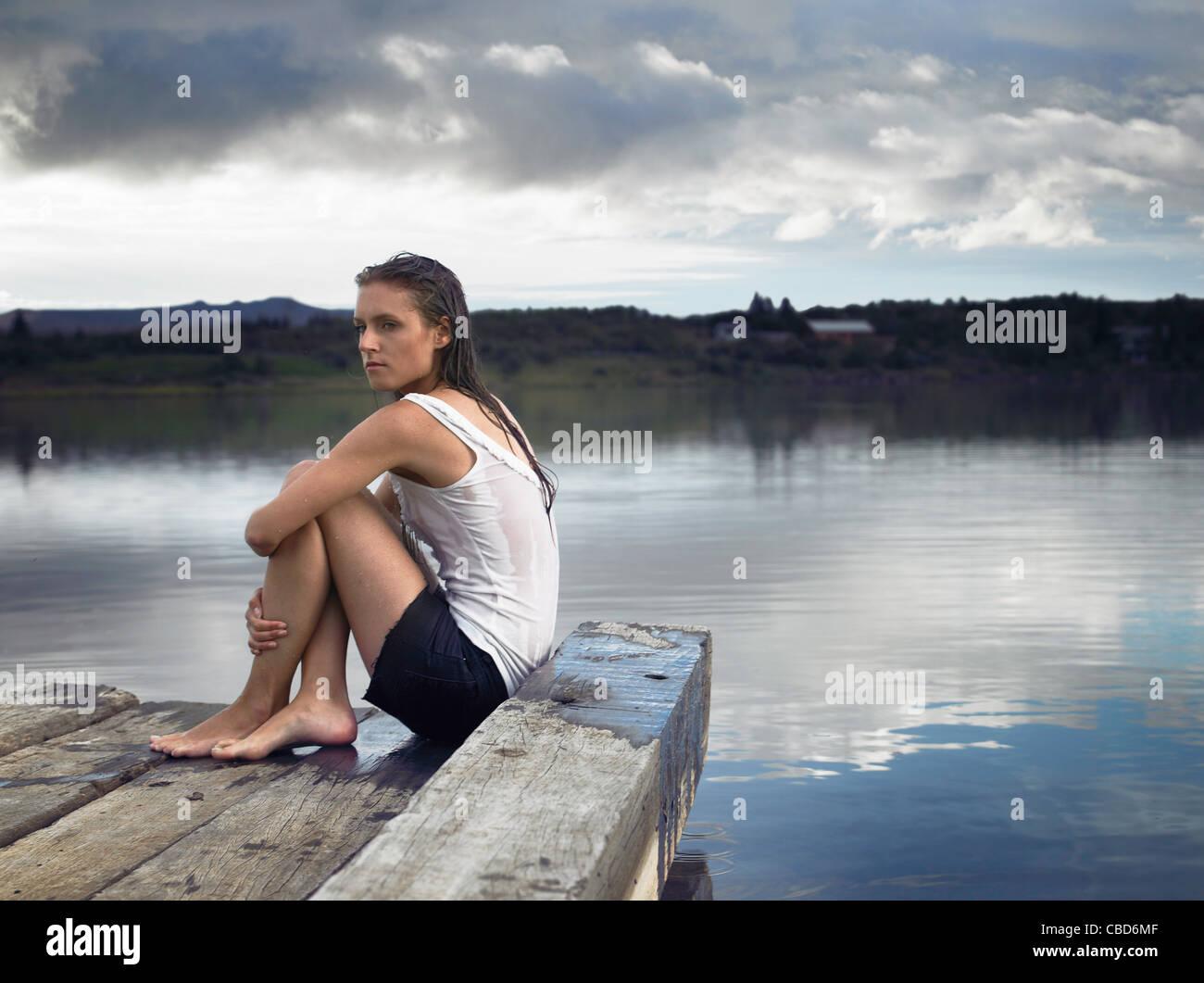 Woman sitting on dock by lake - Stock Image