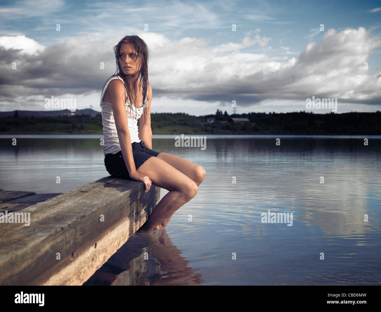 Woman sitting on dock by lake - Stock Image