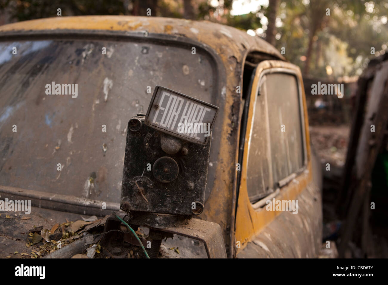 India, West Bengal, Kolkata, Rabindra Sarovar, for hire sign of derelict Hindustan Ambassador taxi buried in rubbish - Stock Image