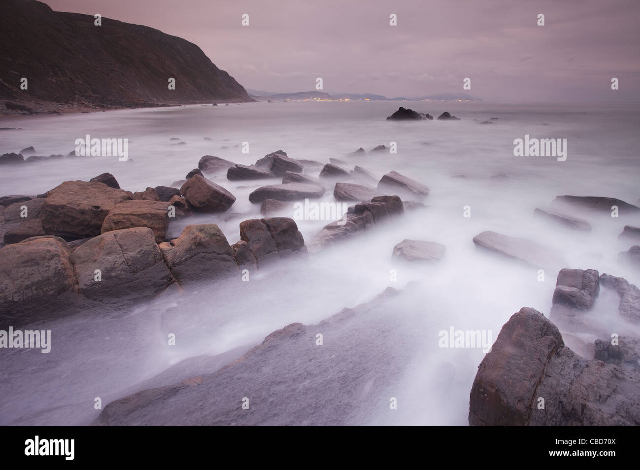Fog rolling over rocky beach - Stock Image