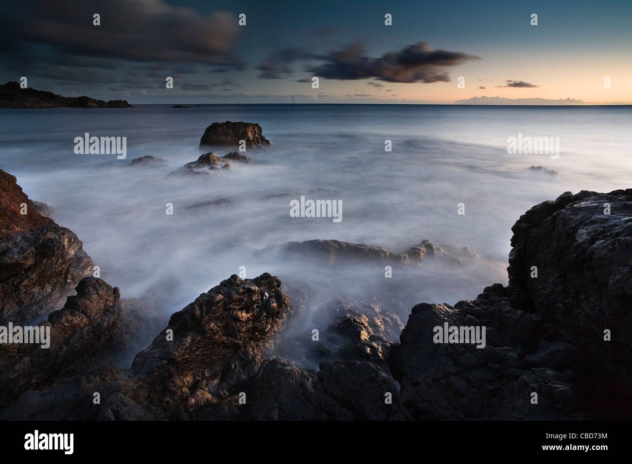 Time lapse view of waves on rocky beach - Stock Image