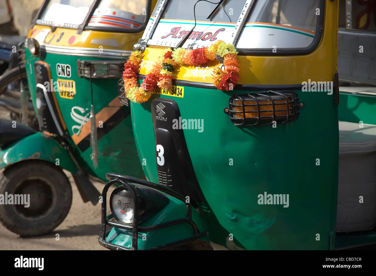 Three-wheeler scooter vehicle traditional Indian transport auto colorful garlanded - Stock Image