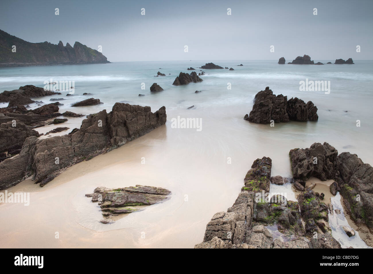 Waves washing up on rocky beach - Stock Image