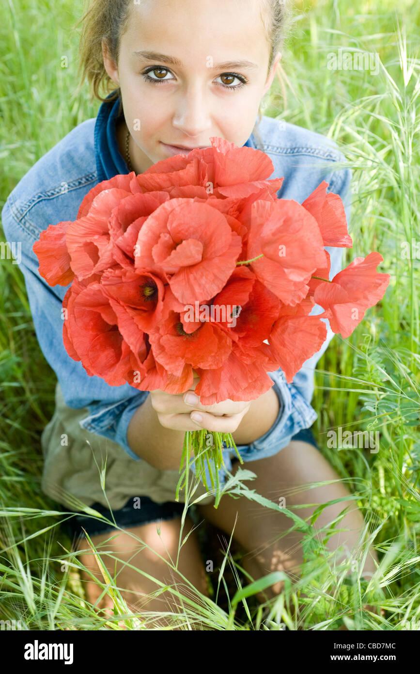 Teen girl kneeling in grass, holding bouquet of fresh poppies - Stock Image