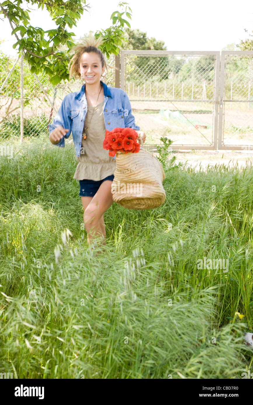 Teen girl walking in tall grass, carrying basket of fresh poppies - Stock Image