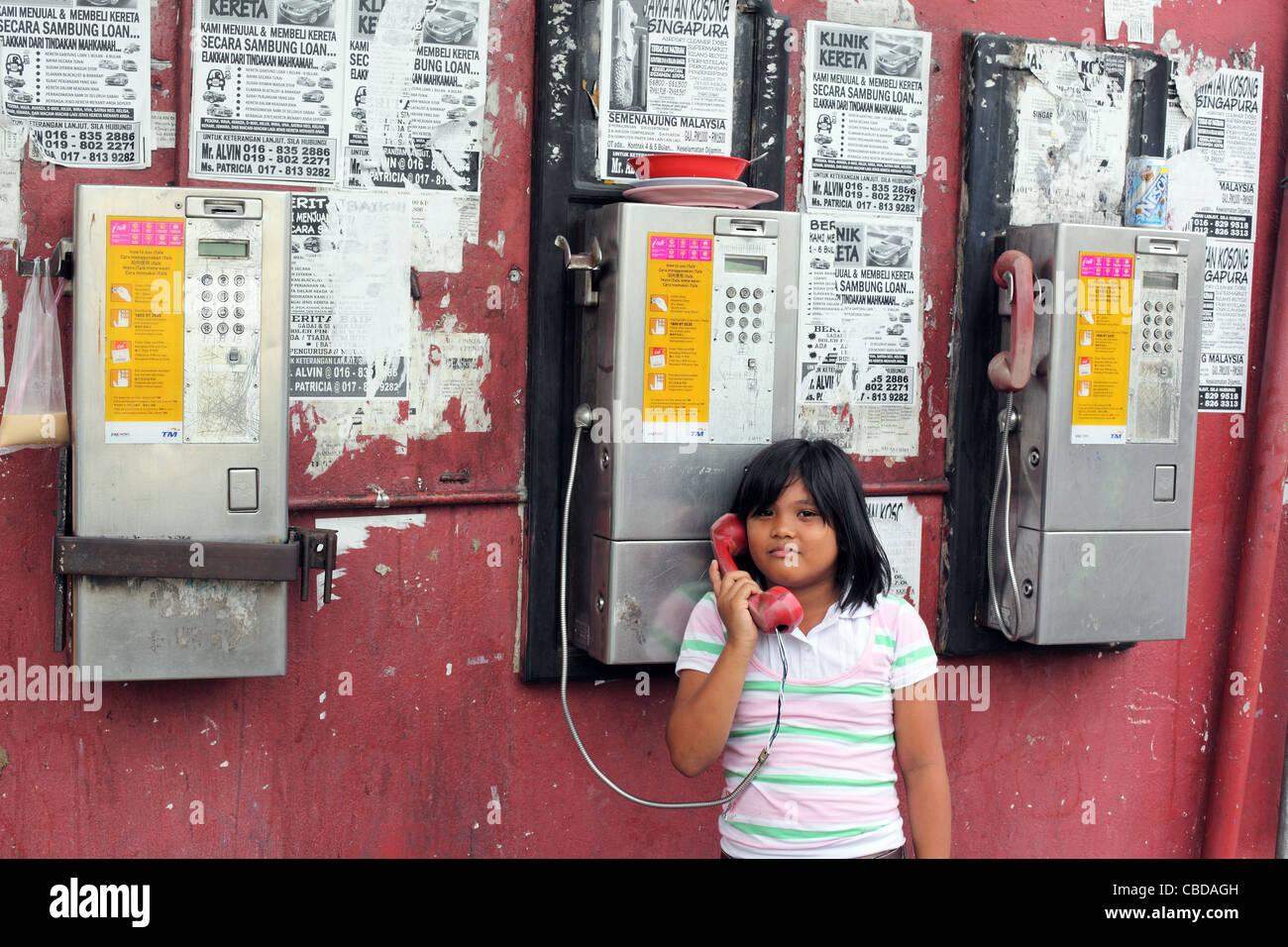 Girl talking on public telephone. Kota Kinabalu, Sabah, Borneo, Malaysia, South-East Asia, Asia - Stock Image