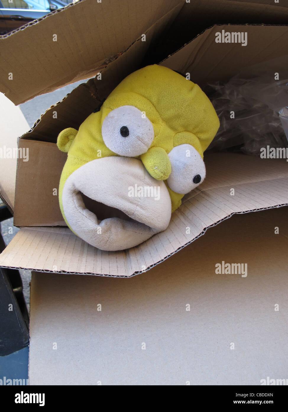 bart simpson slipper shoe dumped in garbage rubbish bin in street road in city town - Stock Image