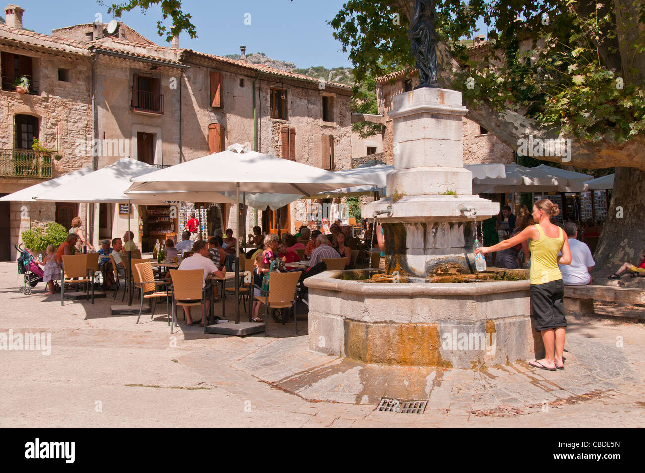 People enjoying drinks on a hot summerday at a pavement cafe by fountain in the hill top village of St Guilhem le Stock Photo