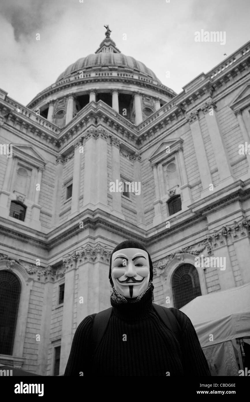 Occupy London protester wearing a Guy Fawkes mask stand in front of the dome of St Paul's cathedral, London. - Stock Image