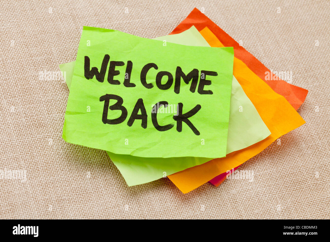 welcome back - handwriting on a green sticky note against canvas board - Stock Image