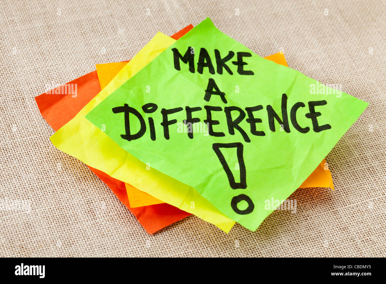 Make a difference -motivational reminder on green sticky note against canvas board - Stock Image